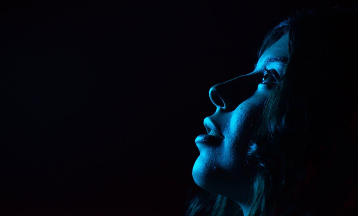 Luz azul de un dispositivo electrónico impactando sobre la piel de una mujer